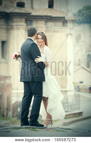 Married couple with wedding dress in the city embraced in the historic center of Rome, Italy. The bride holds a bouquet of flowers in hand. She is smiling. The groom is the shoulders.