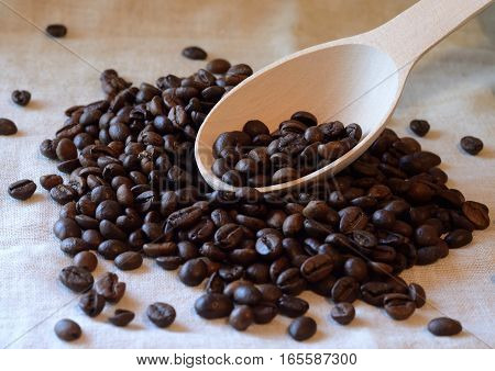 Brown roasted coffee beans and wooden spoon on piece of linen textile - food background