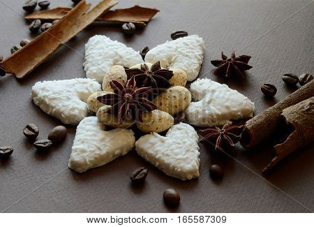 Star made of white coconut heart shaped biscuits with chocolate almond candies and anise spicescinnamon sticks and coffee beans still lifeholiday food background