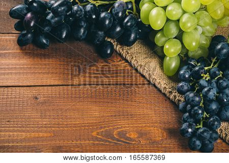 Bunch Of White And Blue Grapes With Burlap On Wooden Background