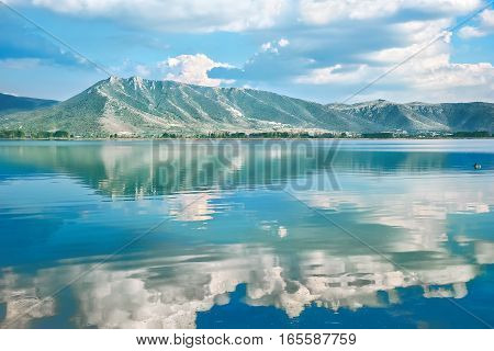 Picturesque landscape with lake Orestiada and the reflection of green mountains and white clouds in the blue water. Greece Macedonia Kastoria
