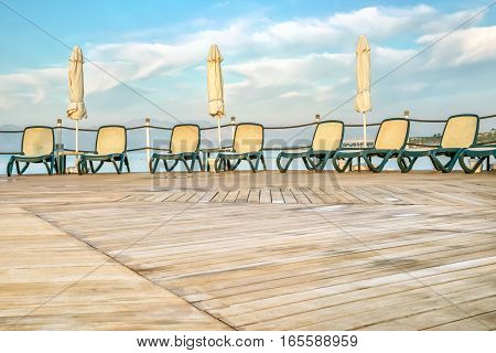 Deserted solarium with wooden decking sun loungers and folded sun parasol after a rain on a background of sea and blue sky with white clouds in a summer day. The foreground is blurred