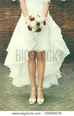 Marry, marriage. Bride outdoors. Bridal bouquet in street. Figure of a woman with a bouquet of flowers in her hand in front of a bricks wall in the city. Cobblestones in the street.