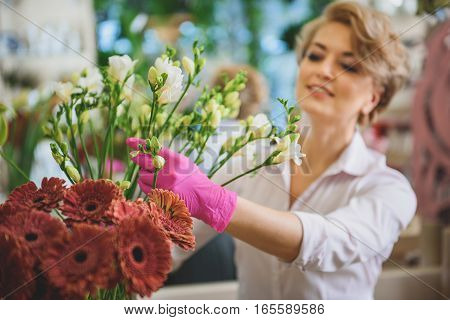 This would be wonderful bouquet. Happy woman is touching flowers with inspiration and smiling. She is standing in her shop