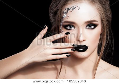 Beauty Woman Portrait. Professional Makeup and Manicure with siver foil glitter, smokey eyes. Black colors. Copy-space. Studio