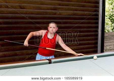 the boy plays billiards in the open air a subject children a game entertainment the resort