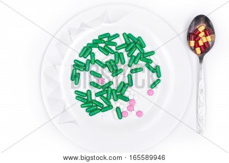 pills are on plate next to spoon with dose of pills. To eat the pills from the plate. Dosage tablets