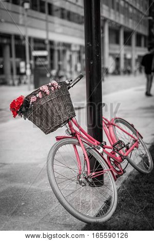 Red and pink bicycle with a basket attached on the street in London centre