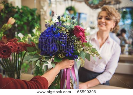 Joyful saleswoman is serving customer and smiling. Focus on beautiful flowers in their hands