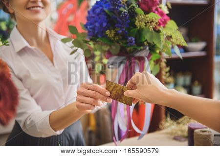 Close up of female hand giving credit card to saleswoman. Florist is holding bouquet and smiling