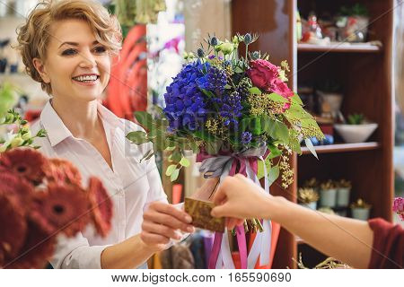 Professional florist is receiving credit card for flowers. She is looking at client and laughing