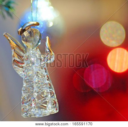 Glass and gold angel against colorful background christmas decoration