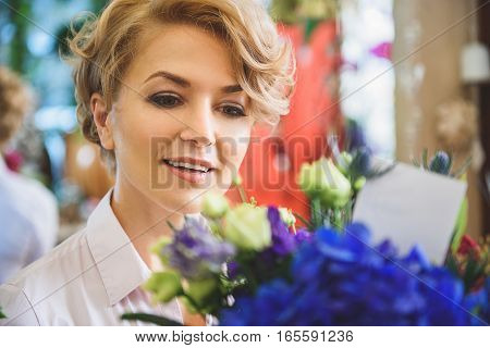 Excited woman is holding flowers and looking at card in it with interest. She is standing with pretty smile
