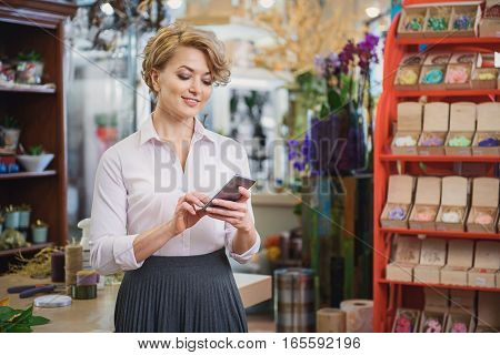 Cheerful woman is messaging on smartphone and smiling. She is standing in flower shop