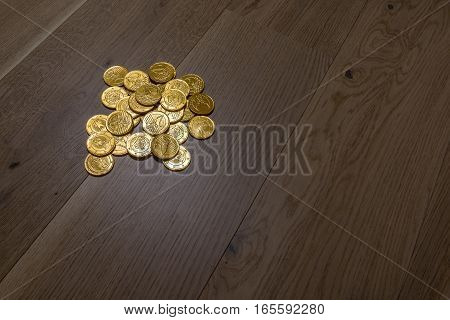 A pile of gold coins shimmer in the light situated on wide oak planks.
