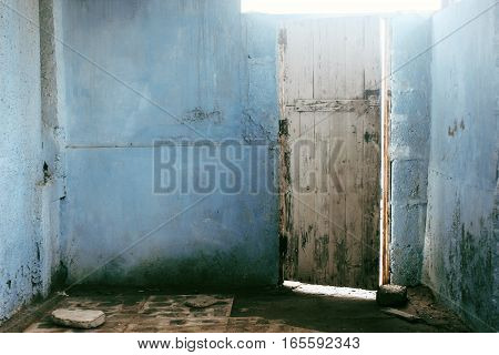 Old textured wooden door on blue walls opening to light