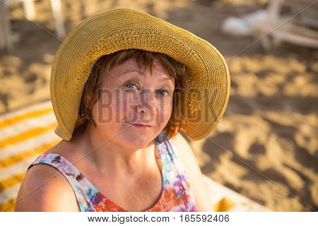 Smiling Senior woman wearing hat. Yellow sunbed on background