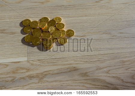 A pile of gold coins on a wooden floor
