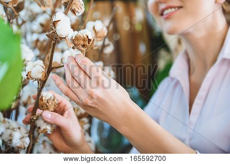 Joyful female florist is taking care of exotic plant. She is touching it and smiling