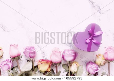 Purple and yellow roses, box present on white background. Overhead view with copy space, toned image