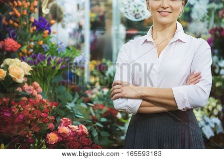 Friendly saleswoman is standing near abundance of roses and smiling