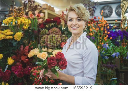 Good choice. Happy florist is holding three red roses and smiling. She is looking at camera with joy