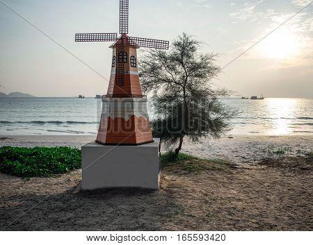 Small wind turbine on the beach at the eastern horizon.