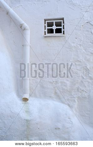 small window and drainpipe in white plastered wall in ostuni italy europe room for your text
