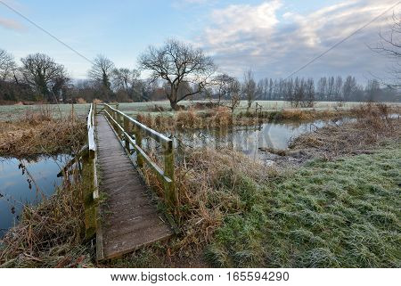 Wooden Footbridge Over A Small River On A Frosty Morning