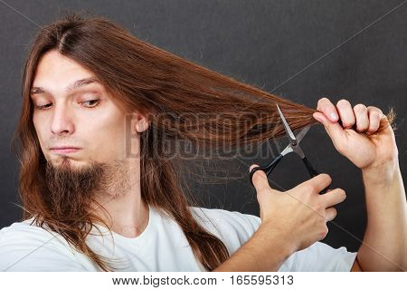 Trim and cut concept. Young handsome man cutting his hair. Change of look. Barber and hairdresser.