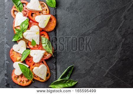 Mediterranean Italian Caprese salad with tomatoes and cheese mozzarella cut as hearts and basil on stone slate plate on slate background. Valentine day menu consept. Healthy food. Top view