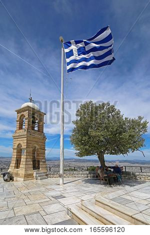 ATHENS GREECE - MAY 02: Greek Symbols at Mount Lycabettus in Athens on MAY 02 2015. Greek Flag Bell Tower and Olive Tree at Top of Mount Lycabettos in Athens Greece.