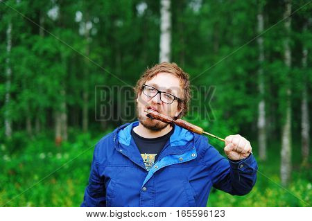 Young bearded man in glasses eating sausages roasted on skewers over a fire in the Park on a background of bright green leaves of trees.