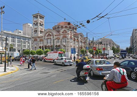 PIRAEUS GREECE - MAY 04: Holy Trinity Cathedral and Traffic in Piraeus on MAY 04 2015. The Holy Church of Agia Triada and Traffic Jam at Junction in Piraeus Greece.