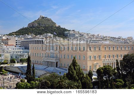 ATHENS GREECE - MAY 03: Greek Parliament in Athens on MAY 03 2015. Bunch of Tourists in front of Hellenic Parliament Building and Mount Lycabettus in Athens Greece.
