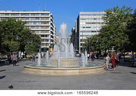 ATHENS GREECE - MAY 04: Fountain at Syntagma Square in Athens on MAY 04 2015. Big Water Jet Fountain and People Walking at Syntagma Square in Athens Greece.