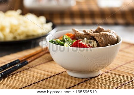 Vegan variation of a ramen noodle soup with veggies ginger and soy meat.