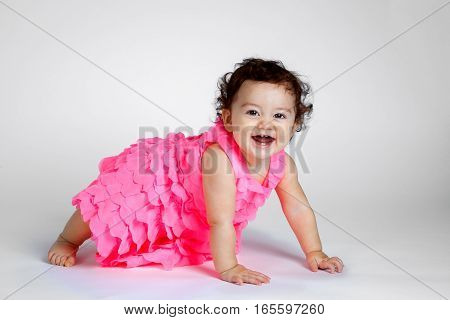 An adorable baby girl on all fours looks at the camera with a huge smile showing all four of her teeth. She has curly brown hair and a pink frilly dress.