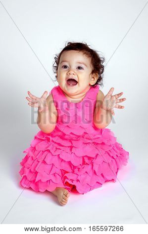 A happy and beautiful baby sits on a white background and blows kisses with hands out. She looks like she could be clapping.