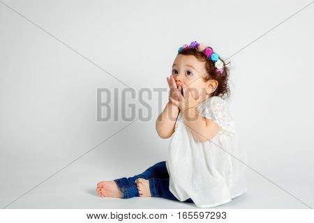 A curly haired brunette baby wearing a floral headband sits on a white background with hands to her mouth. She is blowing kisses.