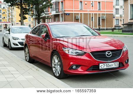 Sochi, Russia - October 11, 2016: New red Mazda 6 (Atenza) parked near modern houses. The Mazda6 has sold over one million units worldwide since its introduction hitting this sales milestone faster than all previous Mazdas.