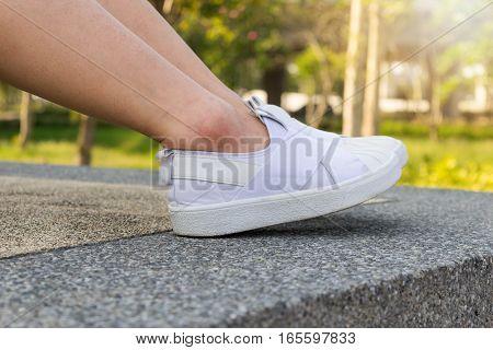 Woman legs wearing white shoes sitting sport.