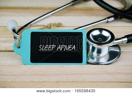 Stethoscope and wooden tag written with Sleep Apnea on wooden background. Medical and Healthcare concept.