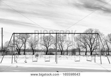 An old metal swingset in an abandoned playground with row of bare trees in rural black and white countryside landscape