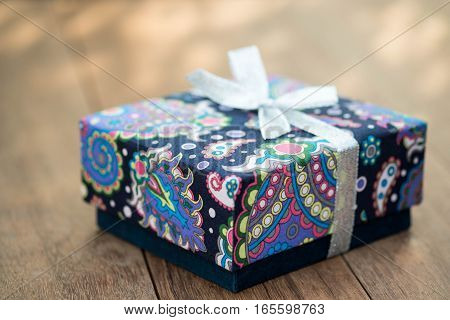 Closeup of wrapped gift box on wooden table.