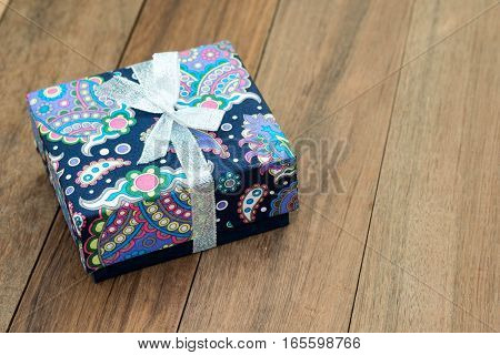 Closeup of wrapped gift box on the wooden background.