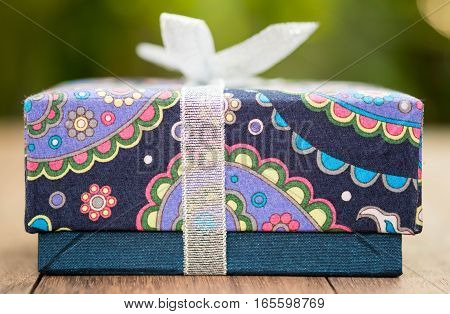 Closeup of wrapped gift box on wood table.