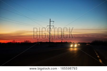 Cars travelling along a curving highway lines with power lines under colorful sunset at night in rural landscape