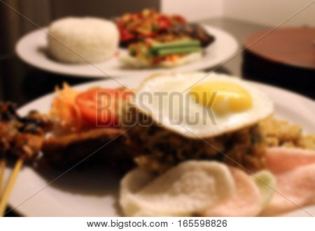 blurred Nasi Goreng and Ikan Gurame bakar fried rice and grilled fish