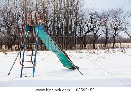 An old weathered metal slide at an abandoned playground in winter